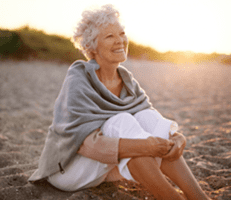 Elderly lady smiling on beach
